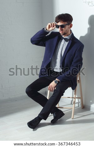 Elegant young handsome man in glasses and watches - stock photo