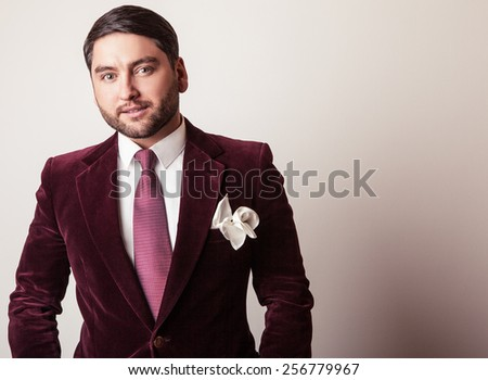 Elegant young handsome man in luxury velvet claret costume. Studio fashion portrait. - stock photo