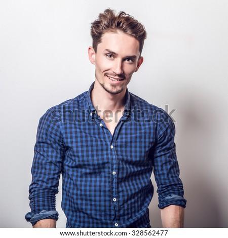 Elegant young handsome man in stylish dark blue shirt. Studio fashion portrait.  - stock photo