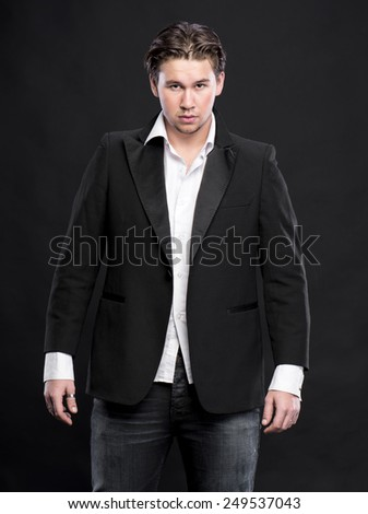 Elegant young handsome man on a dark background - stock photo