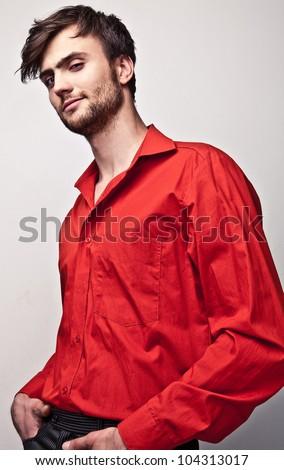 Elegant young handsome man pose on red shirt. Studio fashion portrait. - stock photo