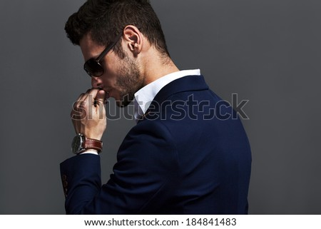 Elegant young handsome man wearing glasses and watchers. Studio fashion portrait. - stock photo