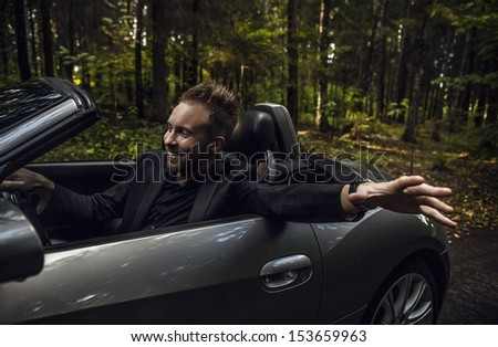 Elegant young happy man in convertible car outdoor. - stock photo