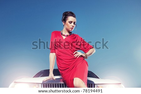 Elegant young lady in front of a white car - stock photo