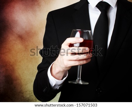 Elegant young man holding a glass of red wine  - stock photo
