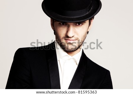 elegant young man in black tuxedo and derby,portrait, studio shot - stock photo