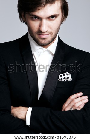 elegant young man in black tuxedo, portrait, studio shot, close up - stock photo