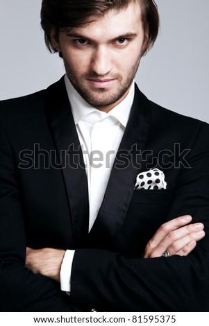 elegant young man in black tuxedo, portrait, studio shot, close up - stock photo