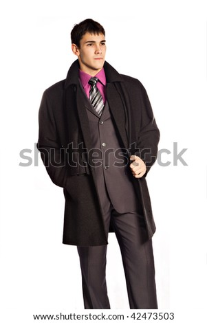 elegant young man in suit and coat, studio on white - stock photo