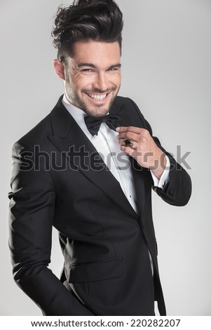 Elegant young man in tuxedo ajusting his bow tie while smiling for the camera. On grey background. - stock photo