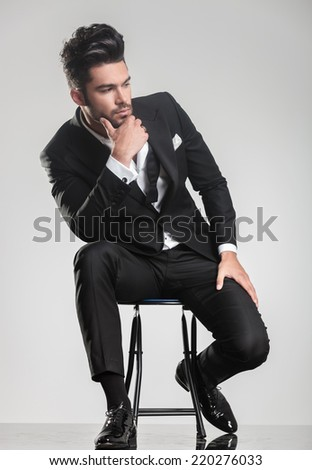 Elegant young man in tuxedo sitting on a stool, looking away from the camera, thinking and holding one hand to his chin. - stock photo