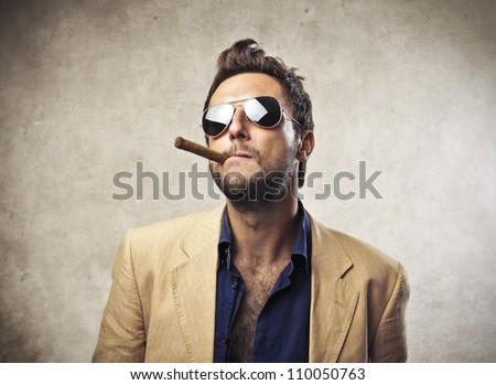 Elegant young man smoking a cigar - stock photo