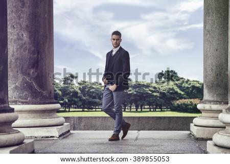 Elegant young man walking near columns - stock photo