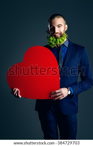 Elegant young man with a beard of green flowers holding red heart and  smiling at camera. Love concept. Valentine's Day. Barbershop. - stock photo