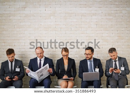 Elegant young people looking for jobs while sitting along brick wall - stock photo
