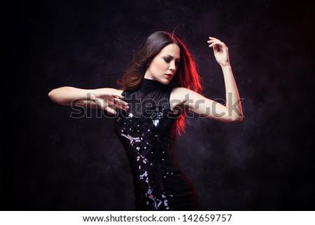 elegant young woman in black dress  dancing red back light studio shot - stock photo