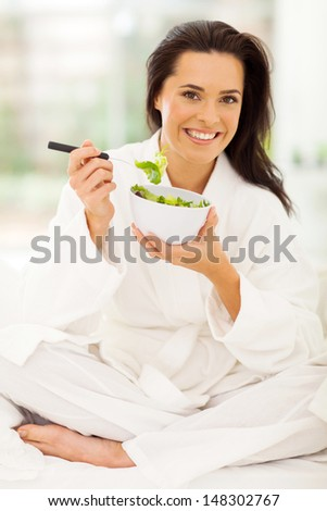 elegant young woman in pajamas eating salad on bed - stock photo