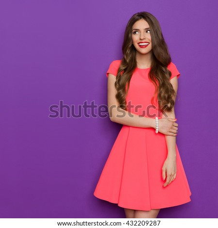 Elegant young woman in pink mini dress looking away and smiling. Three quarter length studio shot on purple background. - stock photo