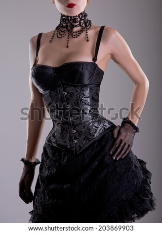 Elegant young woman in silver corset and black skirt, studio shot  - stock photo