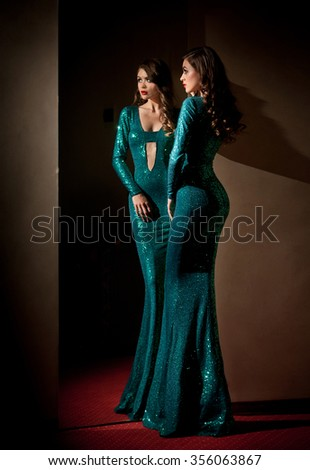 Elegant young woman in turquoise long dress looking into a large mirror, side view. Beautiful slim girl with creative hairstyle posing in front of a wall mirror, indoors shot. Fashionable model. - stock photo