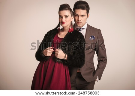 Elegant young woman leaning on her lover while he is looking at the camera with his hands in pockets. - stock photo