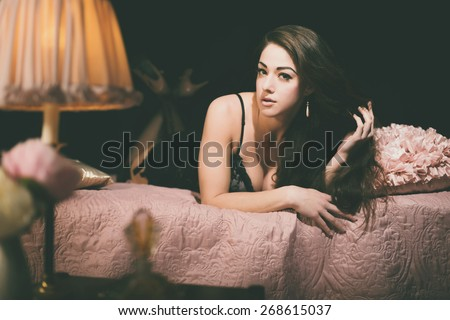 Elegant Young Woman Lying on her Stomach on a Pink Bed While Touching her Hair and Looking at the Camera. Captured Indoor with Black Background. - stock photo