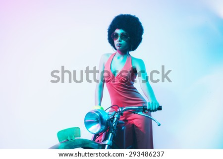 Elegant Young Woman Posing on her Vintage Motorcycle While Smoking a Cigarette Against White Background. - stock photo