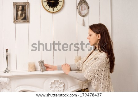 Elegant young woman standing with her arms resting on a marble fireplace staring at on old portrait in a silver frame as she reminisces or pays tribute to a loved one - stock photo