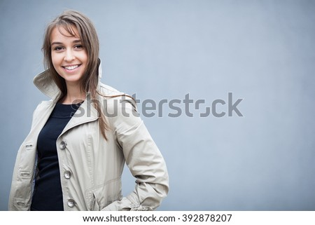 Elegant young woman wearing a trench coat and posing in front of a grey wall (shallow DOF; color toned image) - stock photo
