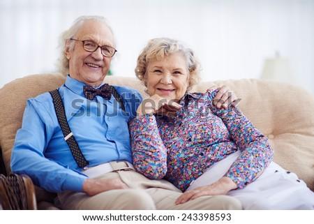 Elegantly dressed happy seniors looking at camera - stock photo