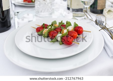 Elegantly served cherry tomatoes kebabs with cheese on the picnic table outdoors - stock photo