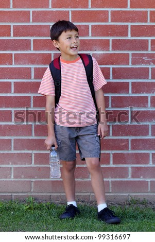 Elementary age school boy waving while waiting next to the red bricked wall of the classroom - stock photo