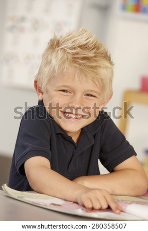 Elementary Age Schoolboy Reading Book In Class - stock photo