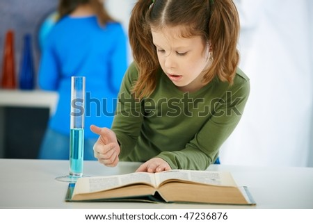 Elementary age schoolgirl looking at book in science class in primary school classroom. - stock photo