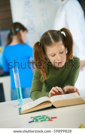 Elementary age schoolgirl looking at book in science class in primary school classroom.? - stock photo