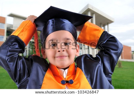 Elementary boy proudly wearing his graduation cap and gown - stock photo