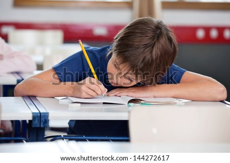 Elementary boy writing in book while leaning on desk in classroom - stock photo