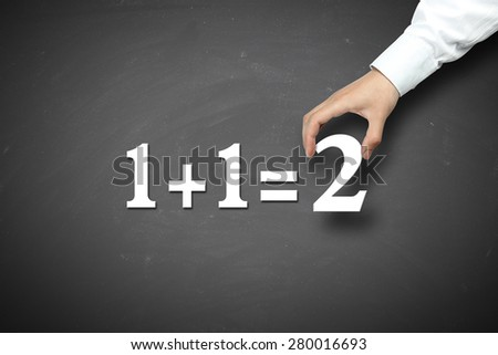 Elementary math concept with businessman hand holding against blackboard background. - stock photo