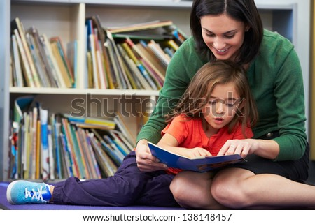 Elementary Pupil Reading With Teacher In Classroom - stock photo