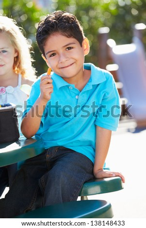 Elementary Pupil Sitting At Table Eating Lunch - stock photo