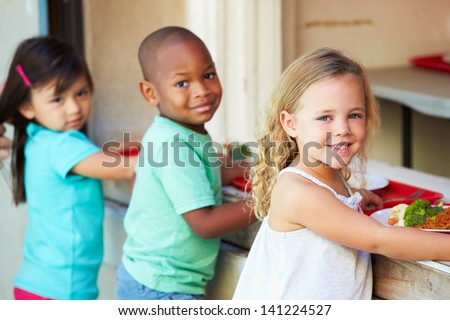 Elementary Pupils Collecting Healthy Lunch In Cafeteria - stock photo