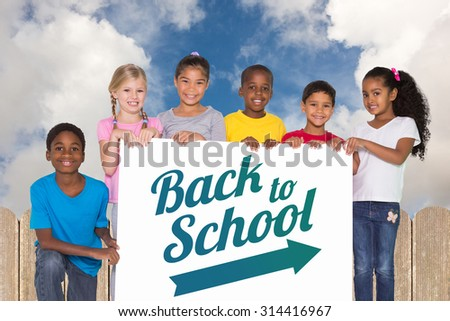 Elementary pupils showing card against fence under blue sky - stock photo