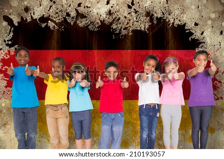 Elementary pupils smiling showing thumbs up against germany flag in grunge effect - stock photo