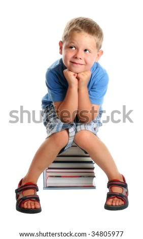 Elementary school age boy sitting on a pile of books, smiling. Isolated on white. - stock photo