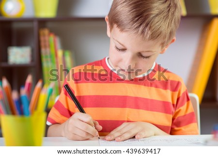 Elementary school boy at classroom desk making homework - stock photo
