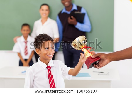 elementary school boy receiving a trophy in classroom with teachers and classmate - stock photo