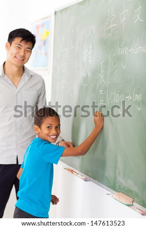 elementary school chinese language teacher and student in front of chalkboard - stock photo
