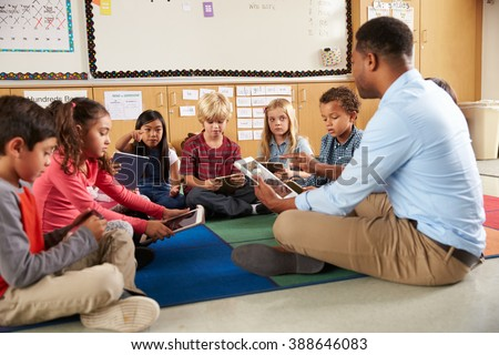 Elementary school class sitting cross legged using tablets - stock photo