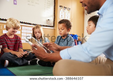 Elementary school class sitting cross legged using tablets - stock photo