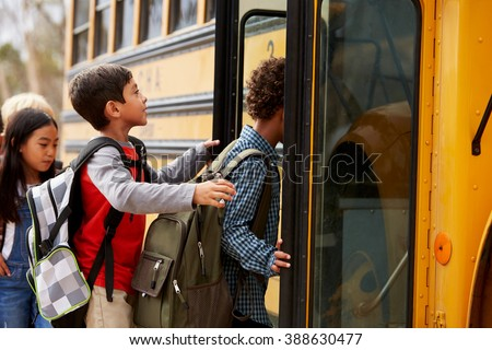Elementary school kids climbing on to a school bus - stock photo